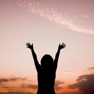 rear-view-of-woman-with-raised-hands-looking-at-the-sky_1160-583